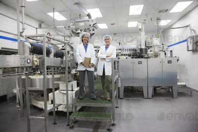 A portrait of two female technicians in the bottling area of a bottled water plant.