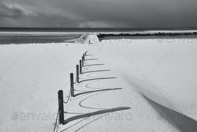 Fence running along a snow-covered beach near the ocean in winter.