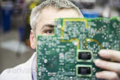 A caucasian male technician examinging a circuit board in a technical research and development site.
