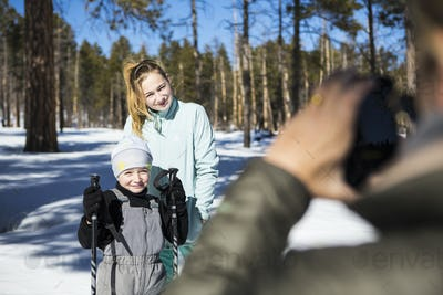 Mother taking a picture of her two children, a boy and teenage girl in snowy forest landscape.
