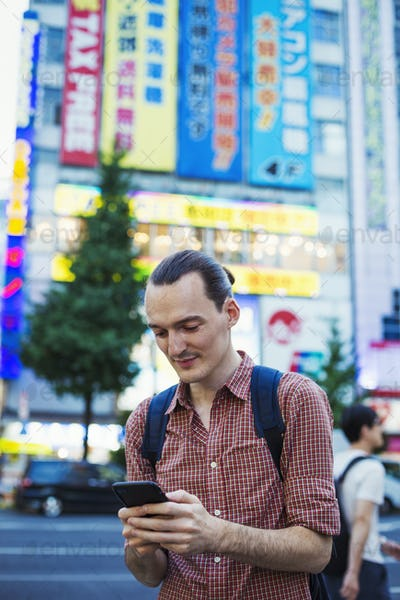 A young man, a Caucasian visitor to Tokyo, on the street holding a smart phone.