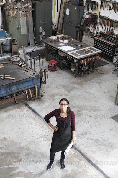 High angle view of woman wearing glasses and apron standing in metal workshop, looking at camera.