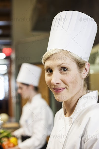 A portrait of a caucasian female chef in a commercial kithchen.
