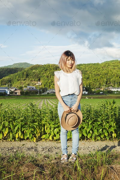 A young woman holding a sun hat, standing on a road by open fields of rice paddies.