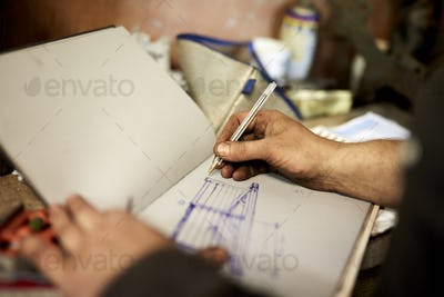 An artisan metal worker drawing up designs for a gate in a sketchbook