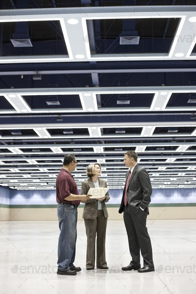 Three business meeting planners talking on the floor of a covnention center space.