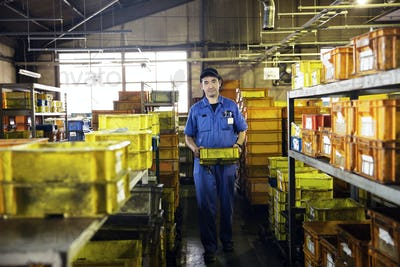 Japanese man wearing baseball cap and blue overall in factory.