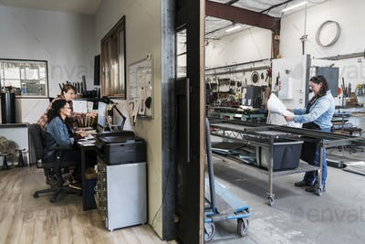 Two women at a desk in office area of a metal workshop, woman standing at mobile workbench.