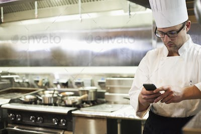 A caucasian male chef checking his cell phone in a commercial kitchen,
