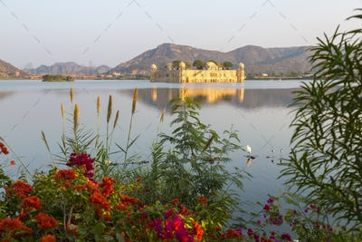 Large water palace in the middle of a lake, red flowers in the foreground.
