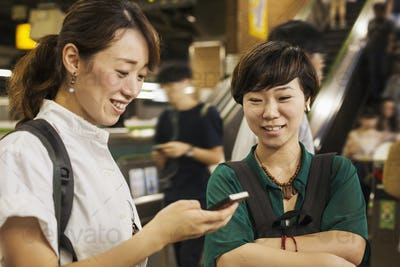Two smiling women with black hair wearing white and green shirt looking at mobile phone.