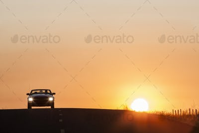 A convertible sports car on a country highway at sunset.