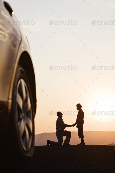 Senior man proposing to a woman while watching a sunset on a road trip.