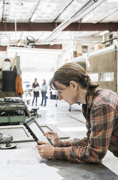 Woman standing at workbench in metal workshop, holding digital tablet.