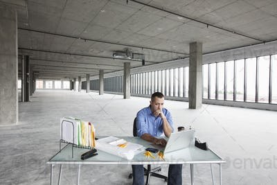 A Caucasian male business owner at his temporary desk in a new raw business space.