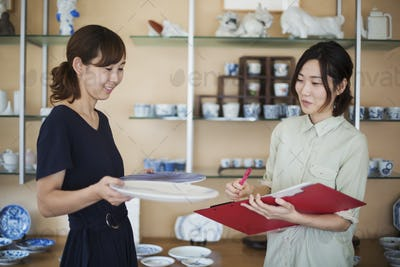 Two women standing in a Japanese porcelain shop, holding plates and document file.