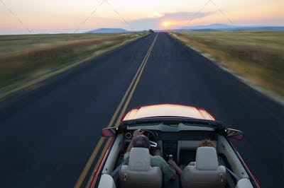 Senior couple in a convertible sports car driving on a highway at sunset