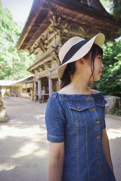 Young woman wearing blue dress and hat standing at Shinto Sakurai Shrine, Fukuoka, Japan.