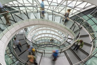Interior view of building with people walking along glass and metal spiral staircase.