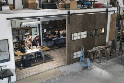 High angle view of two women gathered around table in office area of metal workshop.