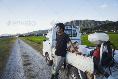 A rice farmer standing by his truck looking across rice paddies and a village in the distance.