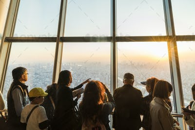 Rear view silhouette of a group of people looking onto cityscape from skyscraper window.
