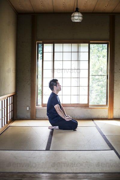 Japanese man kneeling on tatami mat in traditional Japanese house.