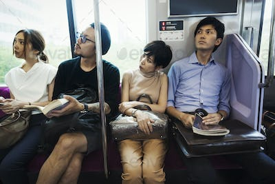 Four people sitting sidy by side on a subway train, Tokyo commuters.
