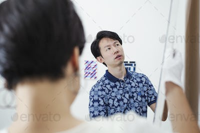 Man in blue shirt and woman hanging modern painting on white wall in art gallery.