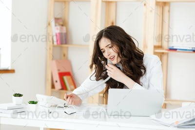 Serious well-dressed saleswoman talking on phone in office behind her desk and laptop computer. Copy