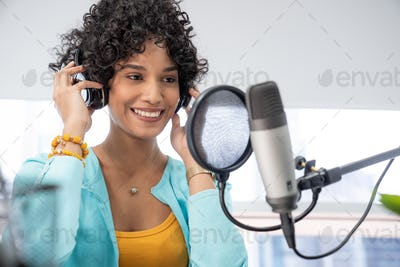 Good looking young black female making an online podcast recording