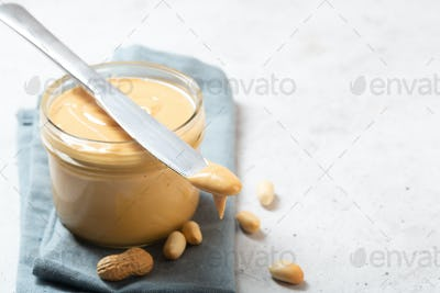 Peanut butter in a glass jar on the table with copy space