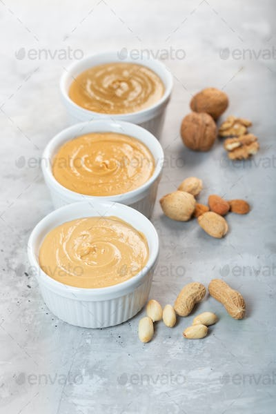 Peanut, walnut and almond butter on the gray concrete background