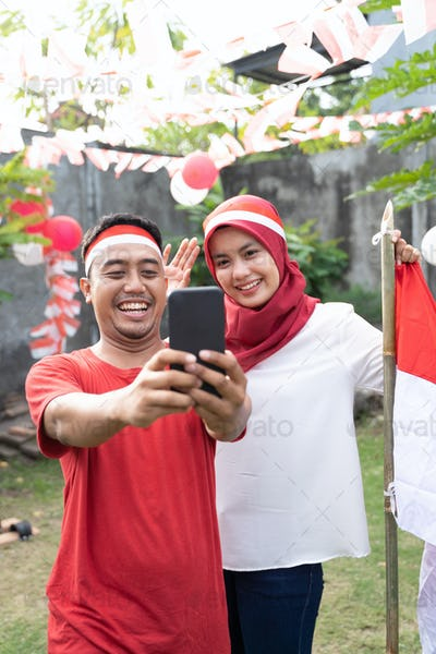 asian young couple take selfies with cameras while wearing red and white attributes