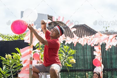young man in a red shirt and red and white headband sit on the stairs to set up balloons