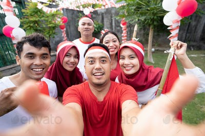 Asian young people smile at selfies with cameras while wearing red and white attributes