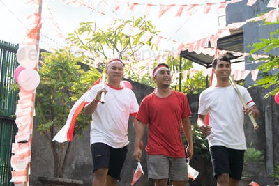 three boys walk while carrying Indonesian flags