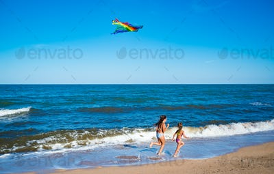 Two little happy cheerful girls run with a kite