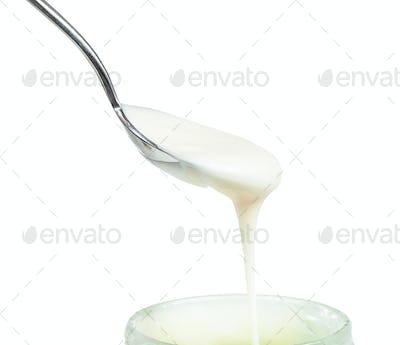 white honey flows from steel spoon in glass jar