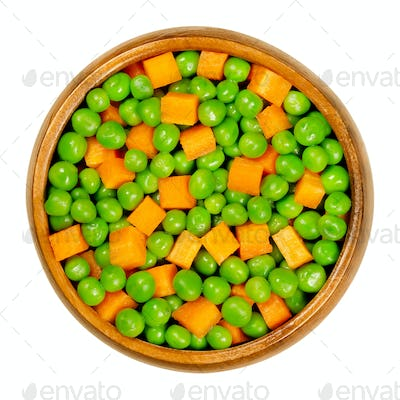 Green peas and carrot cubes, mixed vegetables in wooden bowl