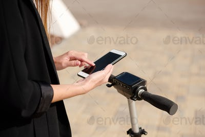 Hands of young female scrolling in smartphone while standing on electric scooter
