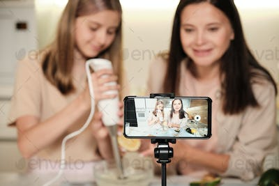 Pretty young woman and her daughter preparing icecream on smartphone screen