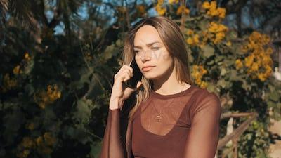 Attractive upset girl patiently listening on the phone outdoor