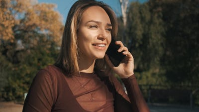 Beautiful smiling girl happily talking on phone with friend during walk along park