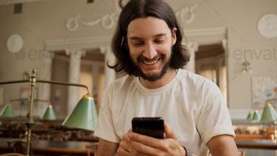 Portrait of cheerful casual student happily using smartphone in library