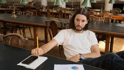 Attractive pensive guy studying alone in university. Thinking expression
