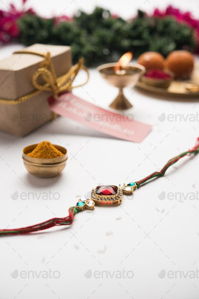Indian festival Raksha Bandhan with rakhi bracelets, presents, rice and kumkum and sweets in plate