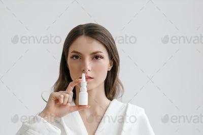 Nose pain spray woman with sick breath. Studio shot.