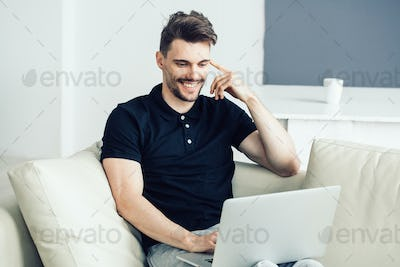 Handsome man with laptop home. Male portrait freelancer working home with computer online