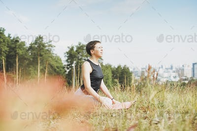 Young smiling woman practice yoga outdoors in the city. New normal social distance